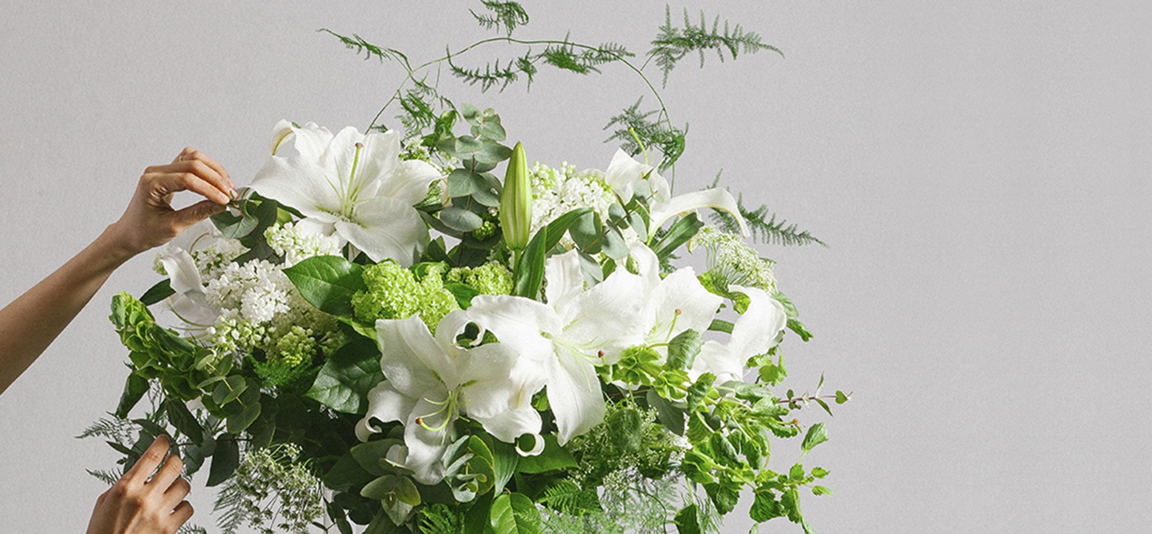 Florist arranging a premium flower bouquet of casablanca lilies. Featuring bespoke bouquet 12.