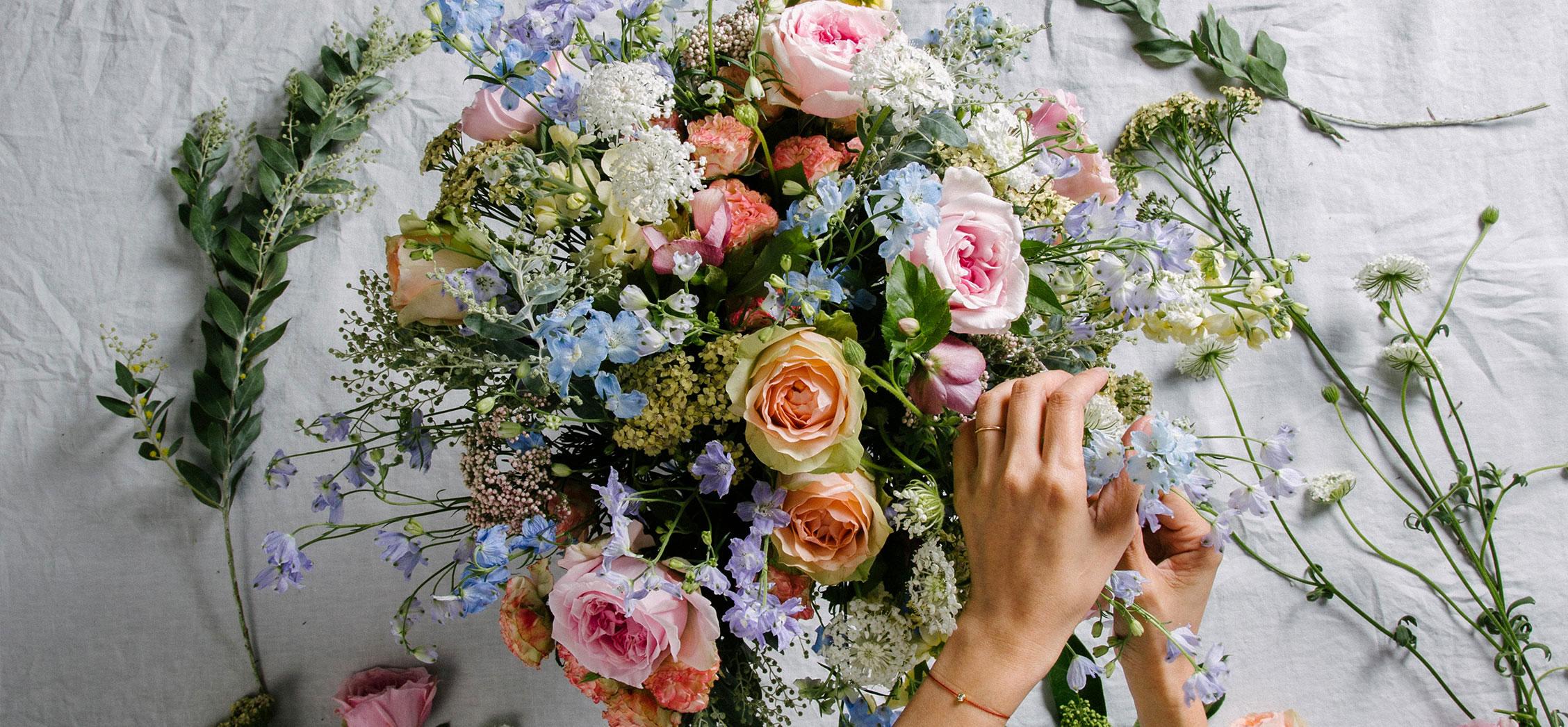 Florist arranging a luxury flower bouquet of garden rose and delphinium. Featuring bespoke bouquet 34.