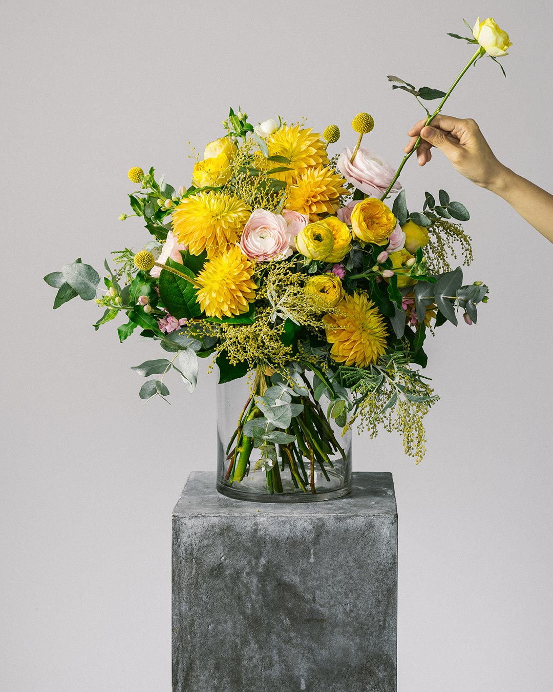 Banner image of florist arranging yellow ranunculus flower bouquet for the bespoke collection