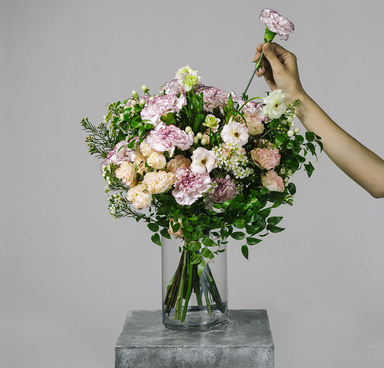 florist arranging a flower bouquet of pink carnation and ranunculus for the bespoke collection