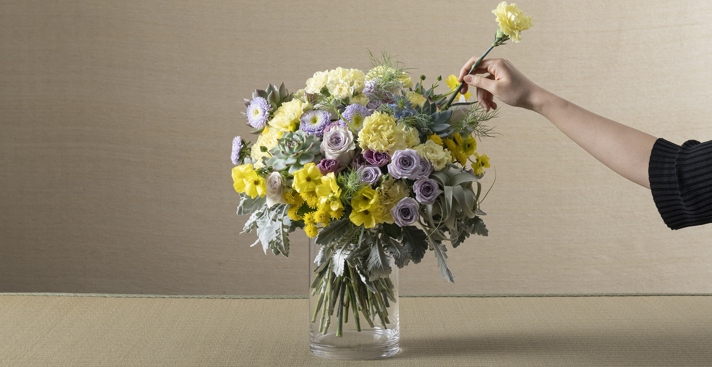 Banner image of a florist arranging Mother's Day flower bouquet of Carnation and Rose for the online flower collection